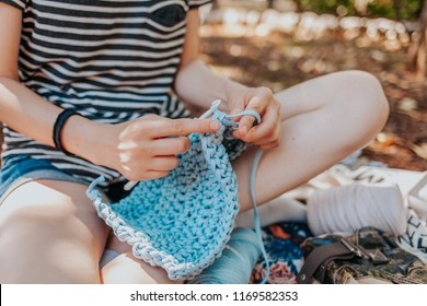 Crocheting outside with fabric yarn, handmade slow fashion, hobby handcrafts