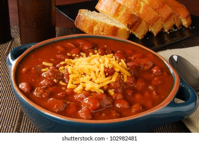 A crock of chili with shredded cheese and cornbread