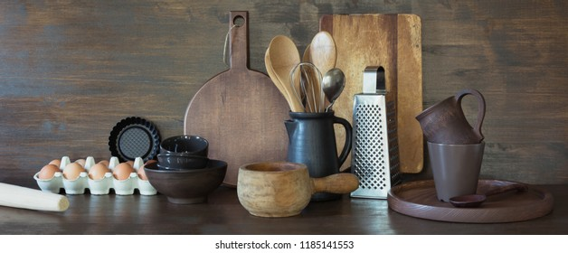 Crockery, clayware, dark utensils and other different stuff for cooking on wooden tabletop. Kitchen still life for cooking as background for design. Copy space.
