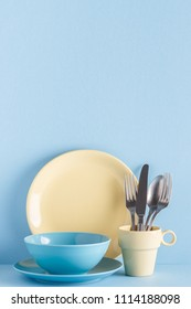 Crockery and cutlery on a blue pastel background with copy space.