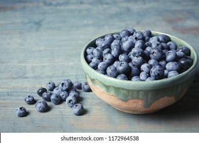 Crockery with juicy and fresh blueberries on wooden table. Space for text