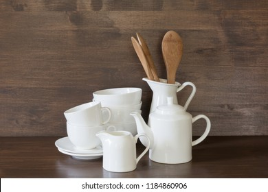 Crockery, porcelain, white utensils and other different stuff on wooden countertop. Kitchen still life as background for design. Copy space.