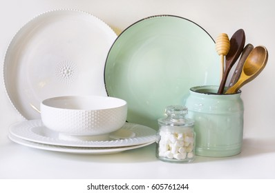 Crockery, tableware, utensils and other different white and turquoise stuff on white table-top. Kitchen still life as background for design. Image with copy space.