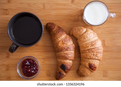 Croissant ant coffee on wooden table
