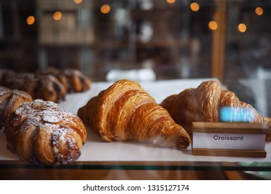 Croissant and bekery in glass shelf in coffee shop with label.