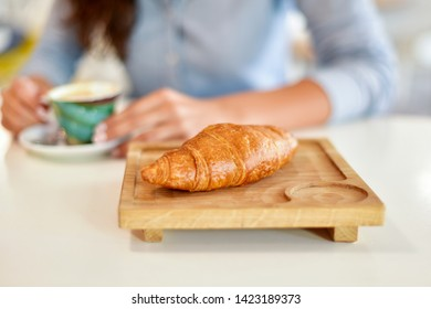 Croissant for breakfast on wooden board