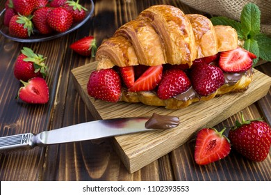 Croissant  with chocolate cream  and strawberry on the  wooden  cutting board