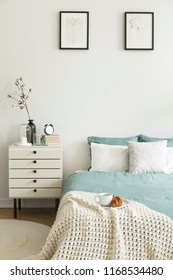 Croissant and coffee for breakfast on a blanket on a bed in a pastel color bedroom interior. Nightstand by the bed. Real photo.