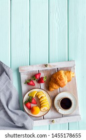 croissant, coffee with fruit for homemade breakfast on the tray on mint green wooden background top view space for text