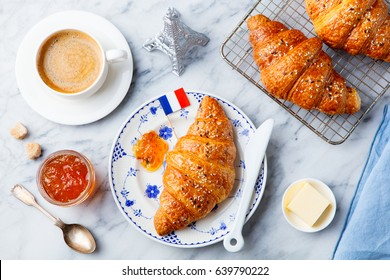 Croissant with coffee, jam, butter and French flag . Continental breakfast concept. Top view.
