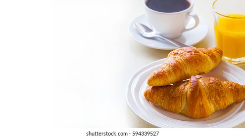 croissant with coffee and orange juice on a white background