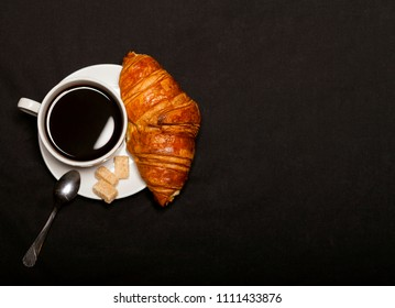 Croissant and cup of coffee on black background with copy space