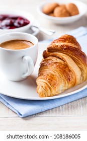 Croissant and a cup of delicious coffee. Sweet dessert. Bright wooden  background. Close up.