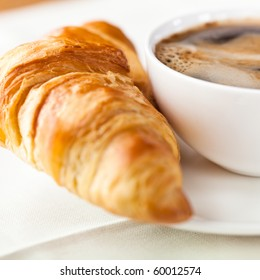 Croissant and a cup of delicious coffee. Sweet dessert. Bright background. Close up.