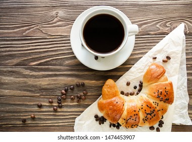 croissant, a Cup of instant coffee and coffee beans on a textured wooden background top view, cozy and delicious Breakfast. Rustic background.