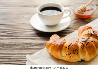 croissant, a Cup of instant coffee and honey on a textured wooden background top view, cozy and delicious Breakfast. Rustic background.