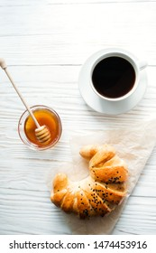 croissant, a cup of instant coffee and honey on a white textured wooden background top view, cozy and delicious breakfast. Rustic background.