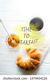 croissant, a Cup of instant coffee and honey on a white textured wooden background with the inscription time to breakfast, top view, cozy and delicious breakfast. Village background.