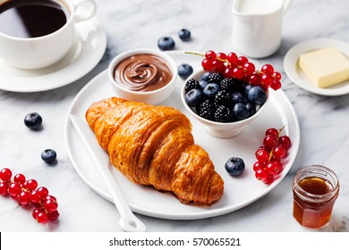 Croissant with fresh berries, chocolate spread and butter with cup of coffee on a marble texture background.