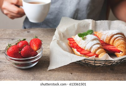 croissant with fresh strawberries, ricotta (cottage cheese) for breakfast on a wooden background. Man holding cup of coffee