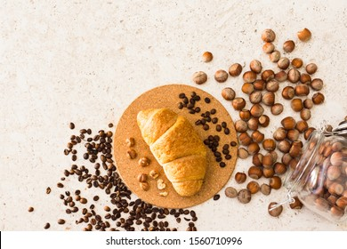 Croissant with hazelnuts and coffee beans on clear background