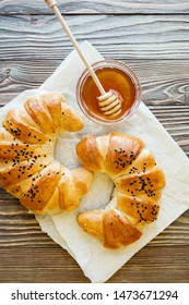 croissant and honey on parchment paper on a textured wooden background top view, cozy and delicious Breakfast. Rustic background.