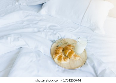 croissant and milk in the wooden tray on the bed breakfast in bed