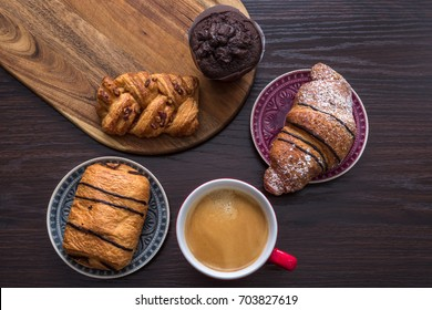 Croissant, muffin, sweet pastries, puff pastry in a wooden background.