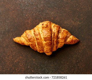 Croissant on brown concrete background. Bakery product. Top view.