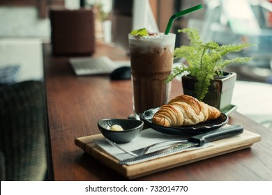 Croissant on dish with iced cocoa on wood table near window at cafe.
