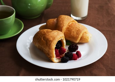 croissant on a large white plate and a glass of milk on dark backraund