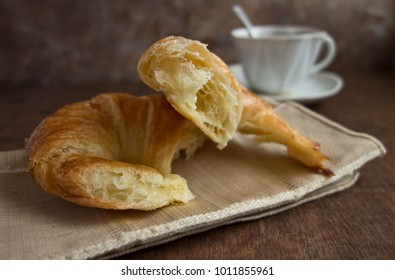 A croissant on linen napkin on wooden table with a cup of coffee.
