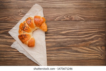 croissant on the textured wooden background top view, cozy and delicious breakfast. Rustic background with copy space.