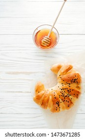 croissant on the white textured wooden background top view, cozy and delicious breakfast. Rustic background.