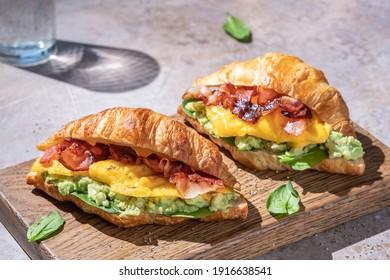 Croissant Sandwich-Frühstück mit Rührei, knusprigem Speck und gemischter Avocado