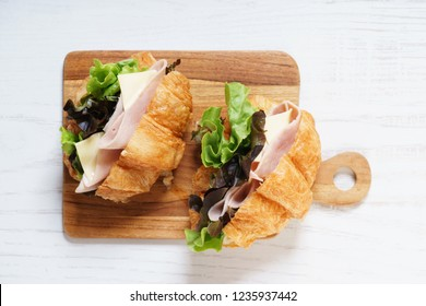 croissant sandwich with ham and cheese on wooden plank