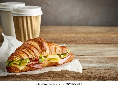 croissant sandwich with ham and cheese and take away coffee cups on wooden table