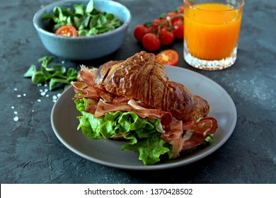 Croissant sandwich with ham and lettuce, fresh juice and salad on dark background. Top view. Delicious and healthy breakfast.