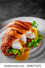 Croissant sandwich with poached egg, tomato and avocado on plate