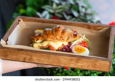 croissant sandwich stuffed with cold smoked salmon and hollandaise sauce served on wooden tray