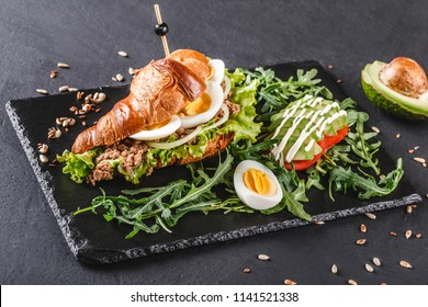 Croissant sandwich with tuna, eggs, avocado, fresh arugula and greens on black shale board over black stone background. Healthy food concept