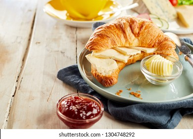 Croissant sliced in half, served with cheese, butter and ketchup in restaurant, on wooden table with copy space