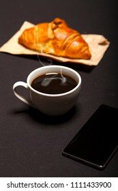 Croissant, smartphone and cup of coffee on a black background