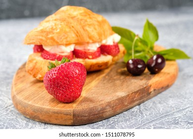 croissant sweet sandwich with cream cheese and strawberries on a wooden board and gray background. Useful breakfast. Proper nutrition. French traditional dishes.