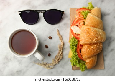 Croissant with vegetables and cup of tea on marble background. Concept lunch.