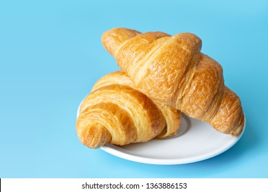 Croissant in a white plate on color background