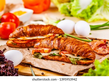 Croissants with bacon, cheese and vegetables on wooden board. Close up