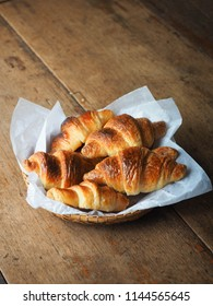 croissants in basket on wood table for breakfast