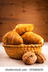 Croissants in a basket on wooden table covered with rough fabric