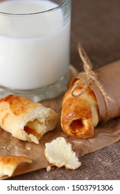 Croissants broken and crumbs with peach jam wrapped in Kraft wrapping paper and tied with strings with bows and a glass of milk on a rough gray tablecloth.